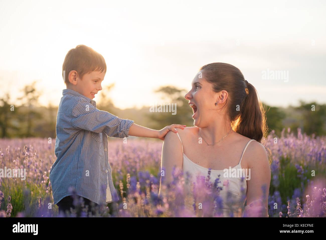 Hermosa emocional madre e hijo tocando su hombro con ternura en el campo de lavanda púrpura en verano cálido Imagen De Stock