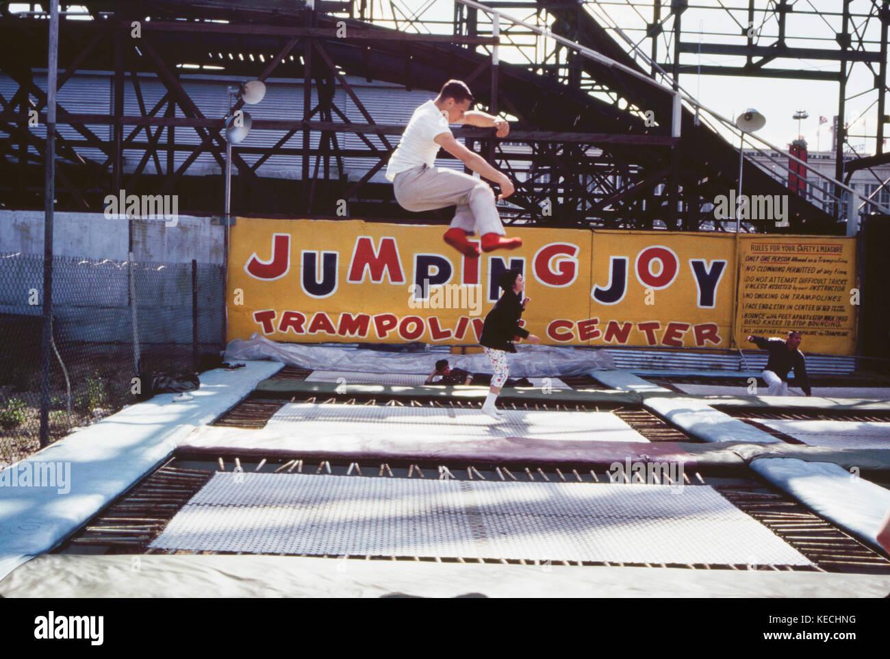 Cuatro personas en trampolines, el parque de diversiones de Coney Island, Nueva York, Estados Unidos, agosto de Foto de stock