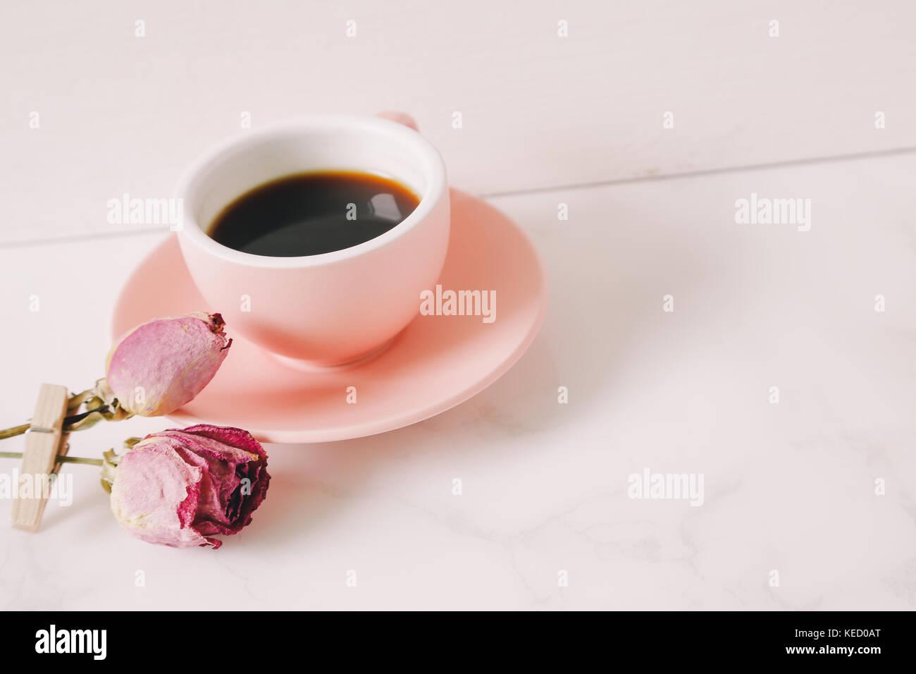 Café y rosa rosa seco sobre la mesa Imagen De Stock