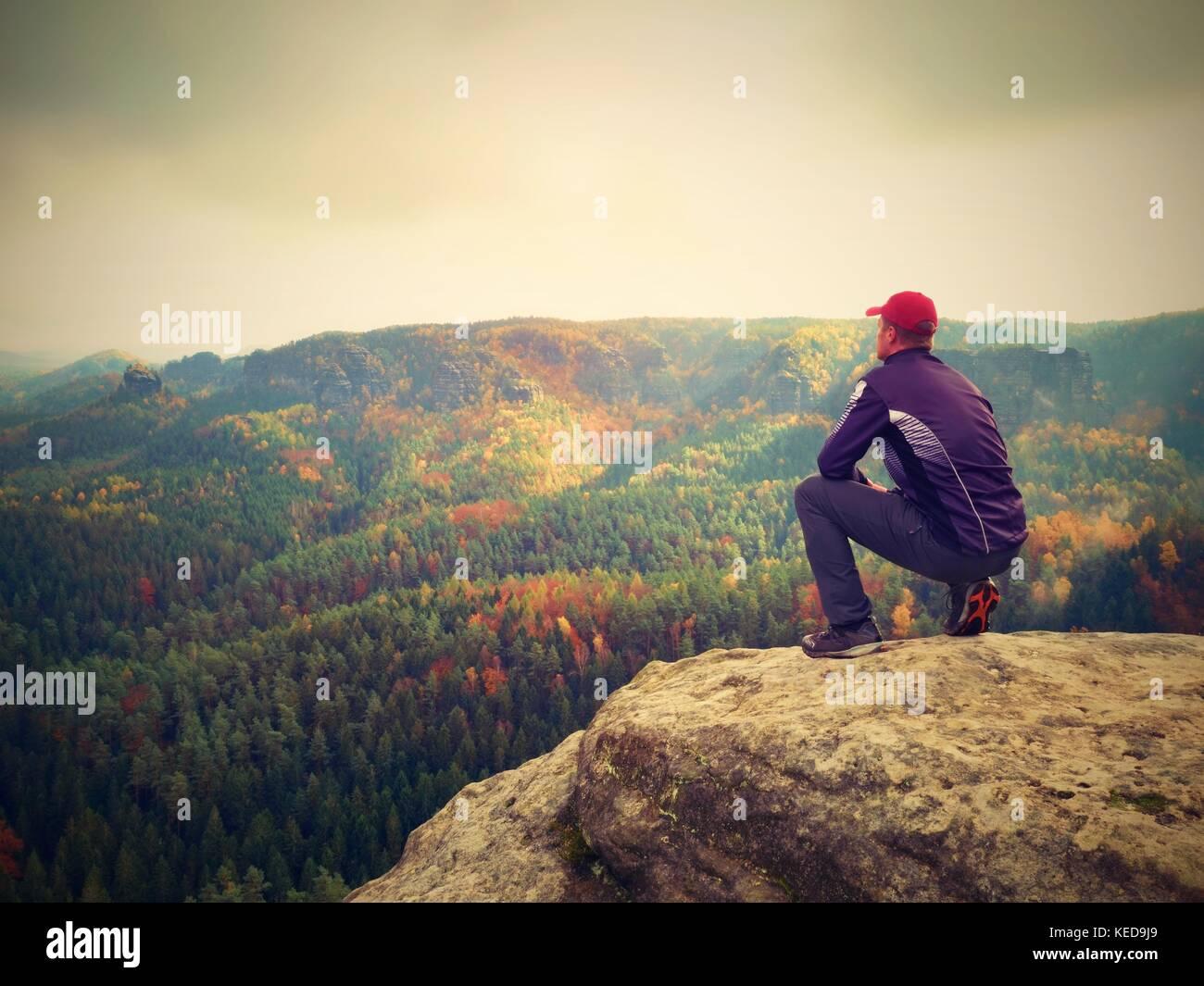 Momento de soledad. Hombre de negro disfrutar de maravillosas vistas. caminante sentarse en la cima de la roca y Imagen De Stock