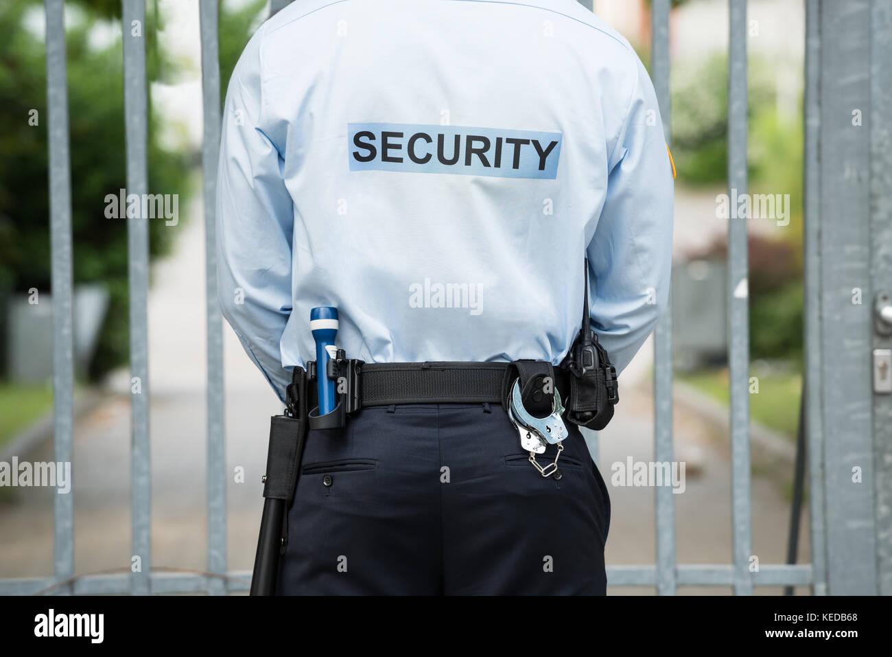 Vista trasera de un guardia de seguridad de pie delante de la puerta Foto de stock