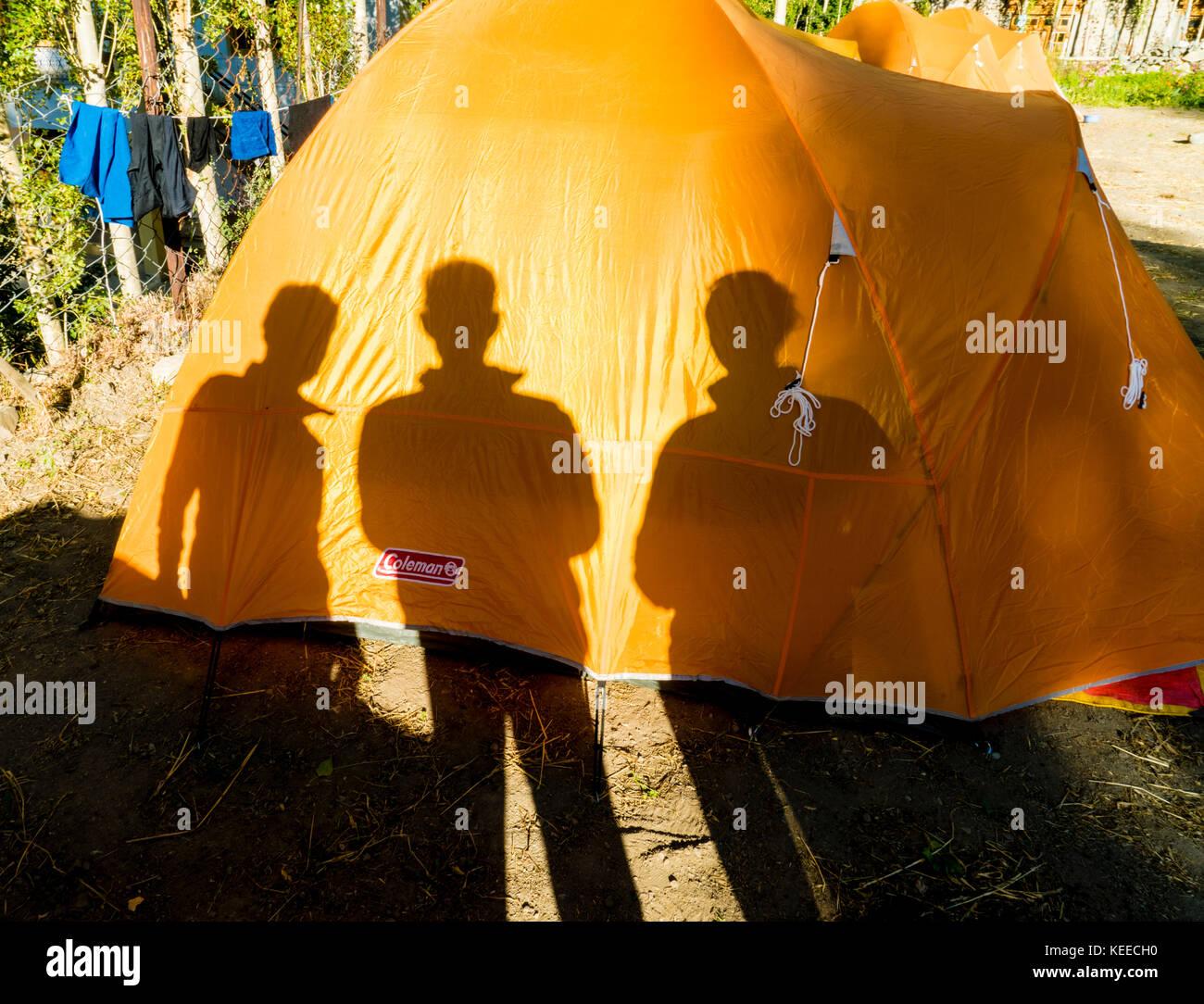 Las sombras de tres personas en una tienda de campaña en un camping en un pueblo en Ladakh, India Foto de stock