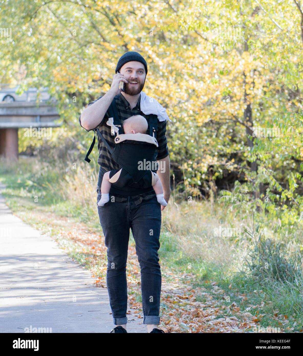 Papá milenaria con el bebé en el portador fuera de hablar y escribir mensajes de texto Imagen De Stock