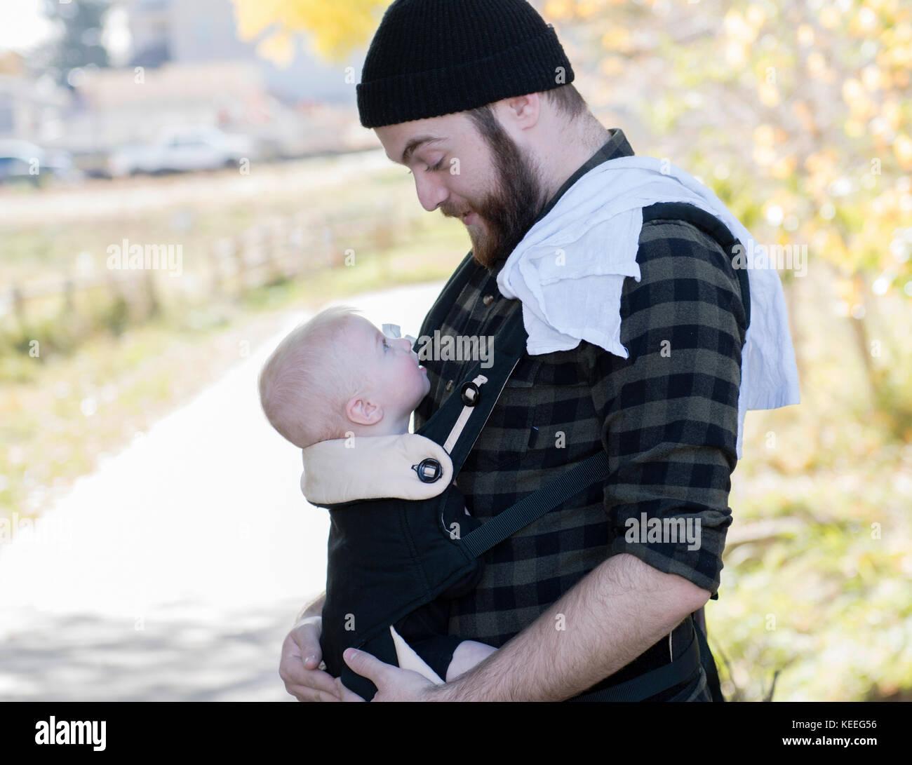 Papá milenaria con el bebé en el portador fuera caminando Imagen De Stock