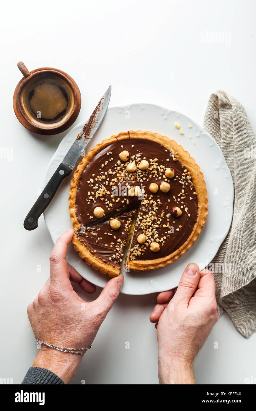 Nogal italiano crostata tarta de chocolate y avellanas y café . las manos del hombre tome un trozo cortado Imagen De Stock