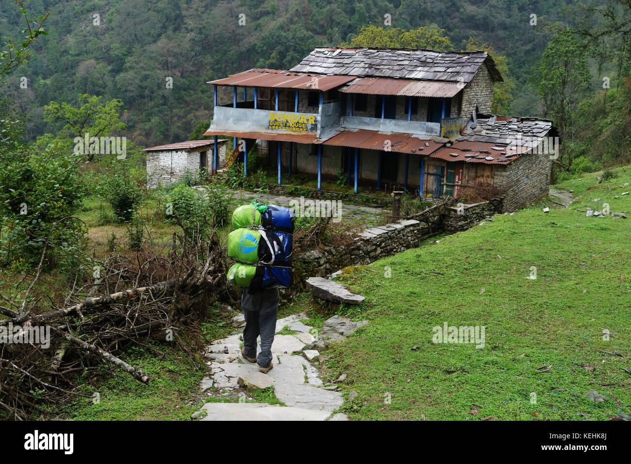 Porter llevando trekker de mochilas en la Poonhill trek, Nepal. Imagen De Stock