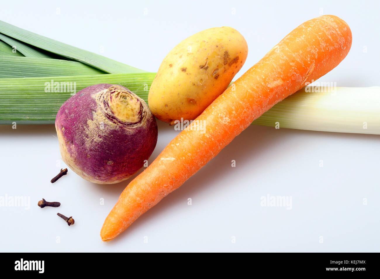 Ingredientes para la receta francesa de pot Au feu: zanahoria, puerro, patatas, nabos, clavo y especias sobre un Imagen De Stock