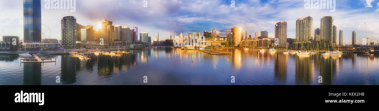 Suburbio de Melbourne Docklands todavía alrededor de la bahía de agua sobre el río Yarra con altos rascacielos torres residenciales y comerciales, reflejando un waterfront Foto de stock