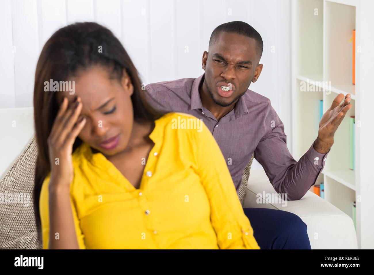 Infeliz joven habiendo argumento con la mujer en el hogar Imagen De Stock