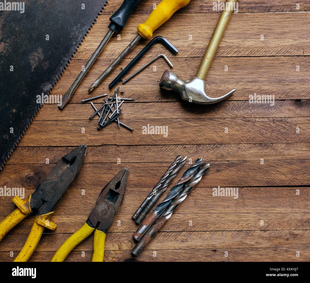 Oxidados y viejos utiliza herramientas de carpintería y garaje sobre un fondo de madera de color marrón claro, mostrando variadas herramientas,con pinzas de metal y vio,brocas metálicas,martillo Foto de stock