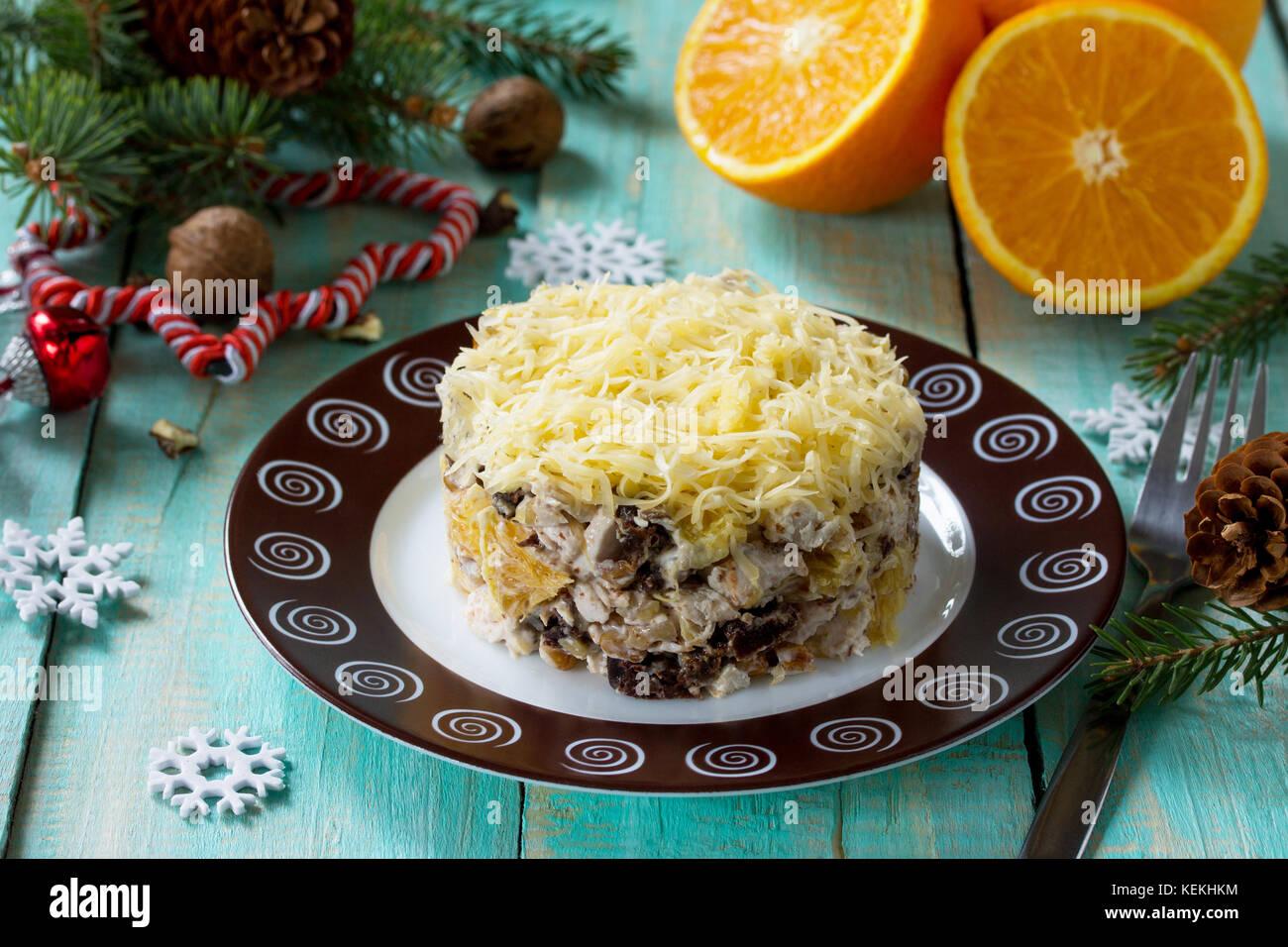 Aperitivos caseros en una mesa navideños. Con ensalada de pollo, naranjas, ciruelas, queso y nueces. Imagen De Stock