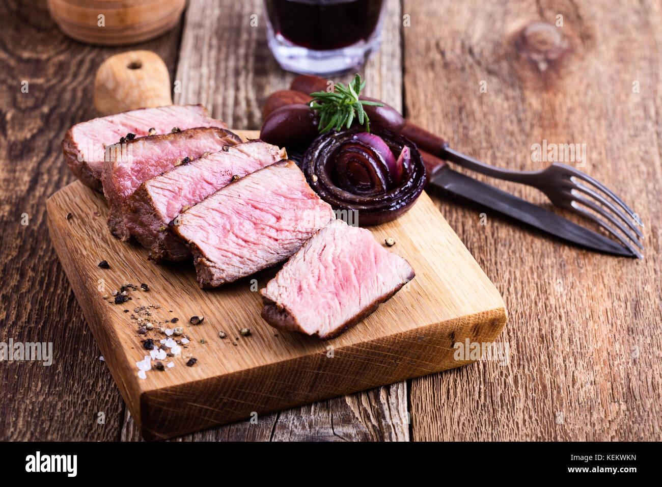 Deliciosa carne filet mignon servido sobre la tabla de cortar de madera con cebolla roja tostada y Romero Imagen De Stock