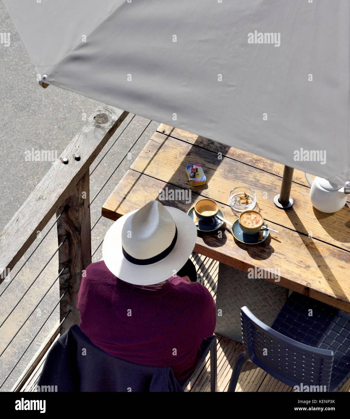 e2e01dd3cbf7f Un hombre que llevaba un sombrero de Panamá sentado con una taza de café  frente al