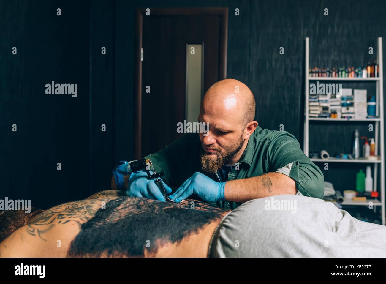 Tatuaje artista principal hace un primer plano del tatuaje. Imagen De Stock