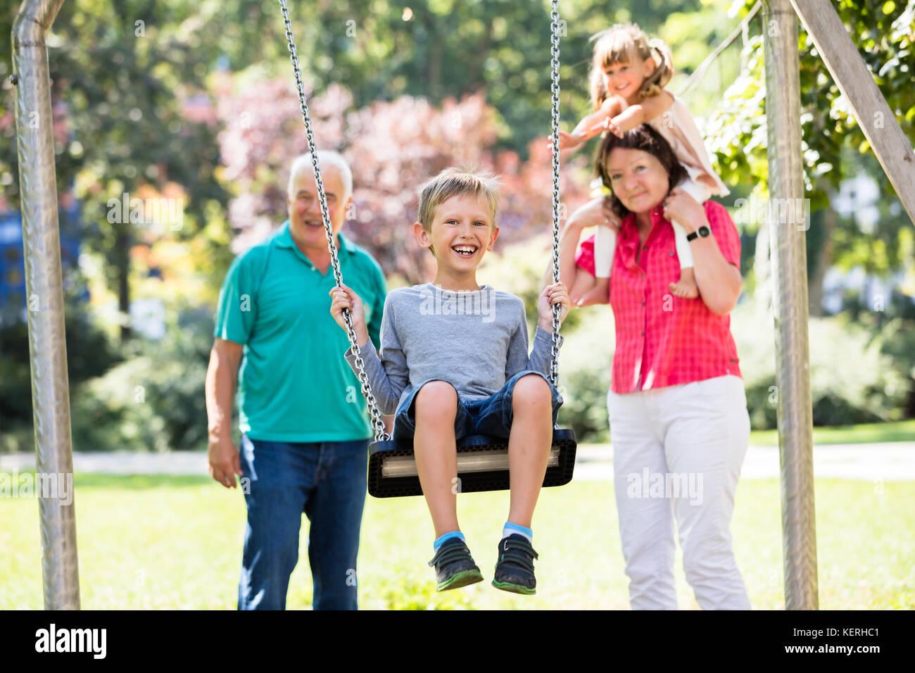 Feliz nieto kid divirtiéndose en swing con viejos abuelos de pie detrás en el parque Foto de stock
