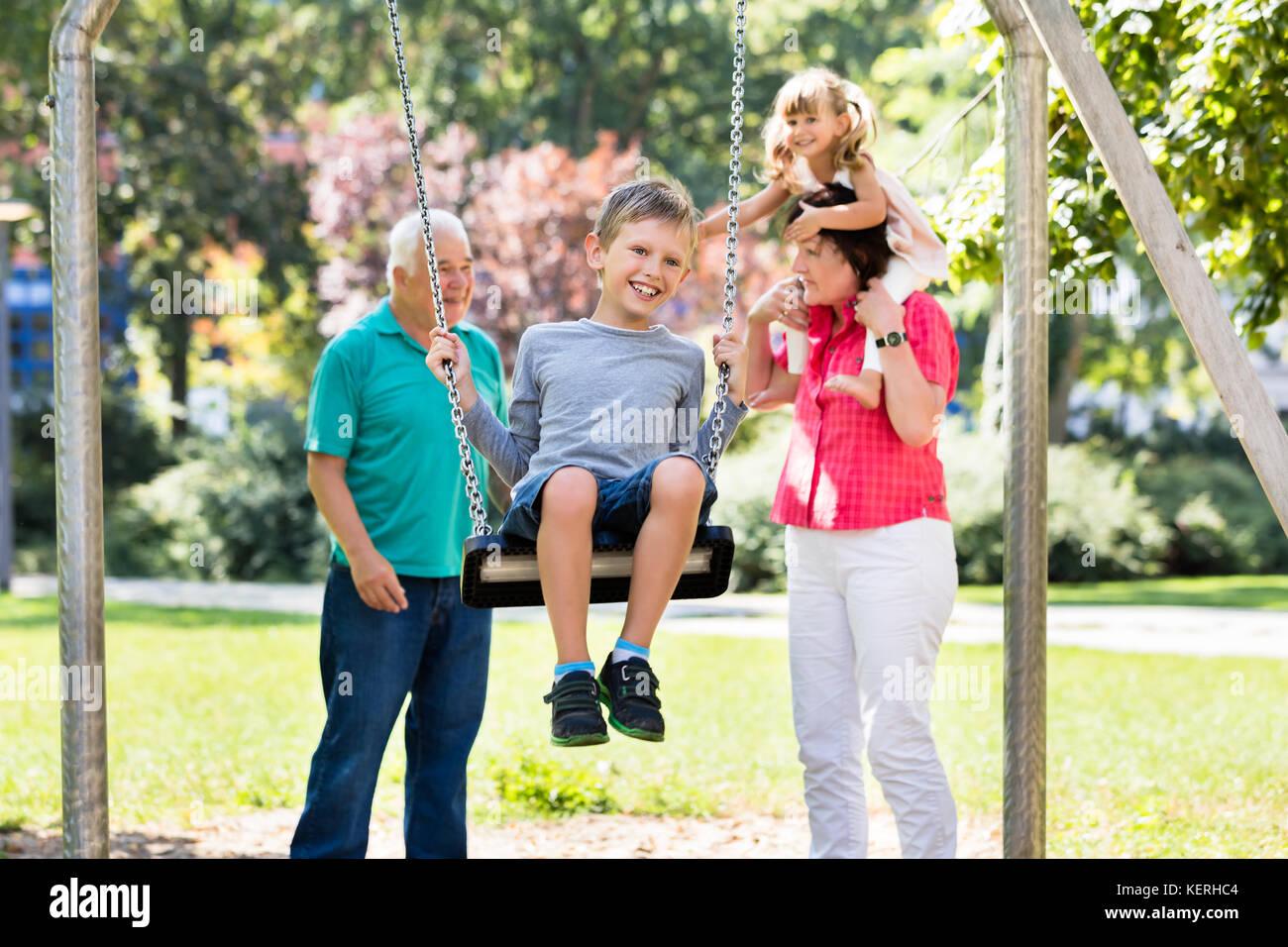 Niño feliz divirtiéndose en swing con abuelos de pie detrás en el parque Foto de stock