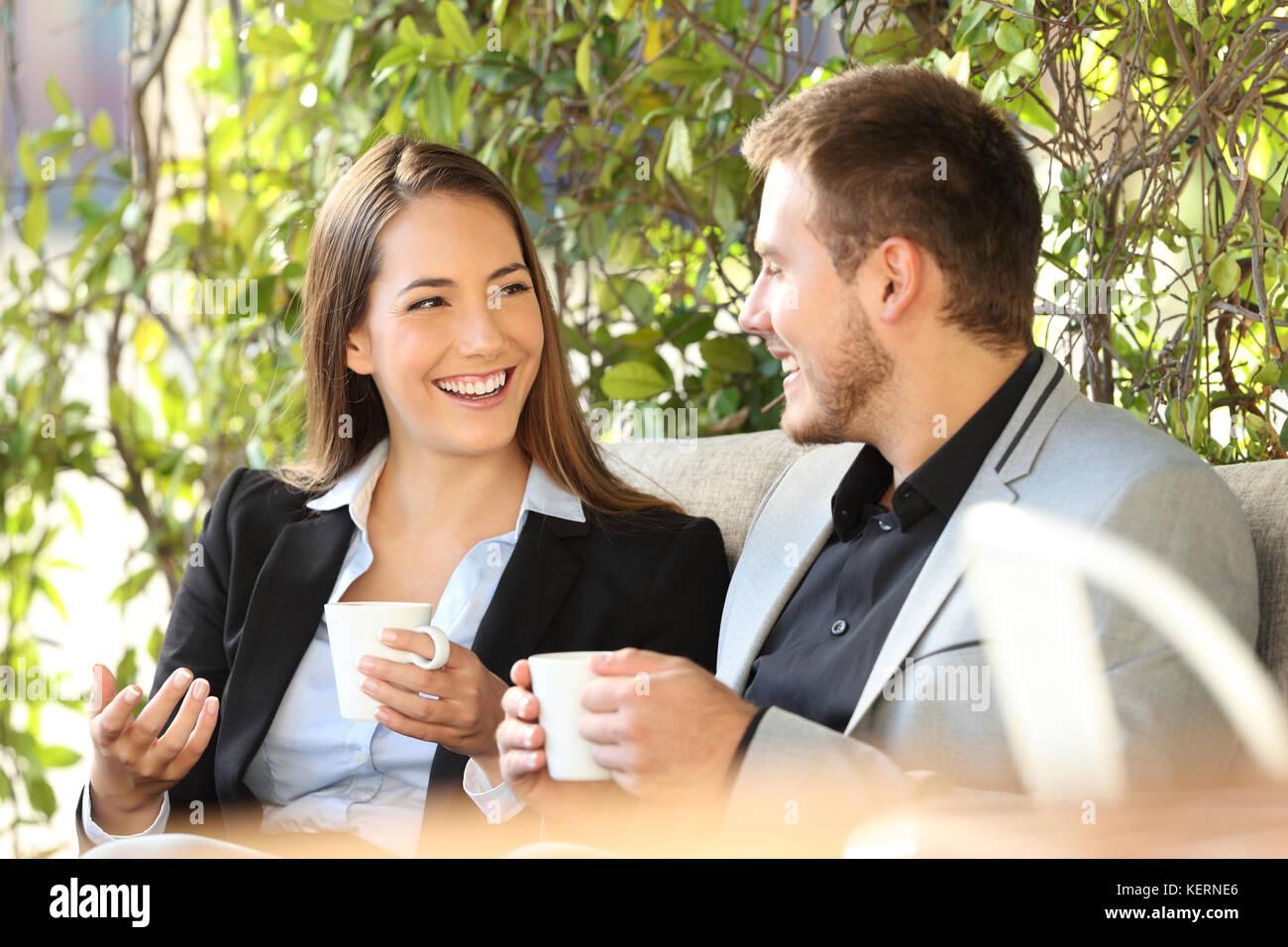 Dos ejecutivos feliz hablando en un café sentado en un bar terraza Imagen De Stock