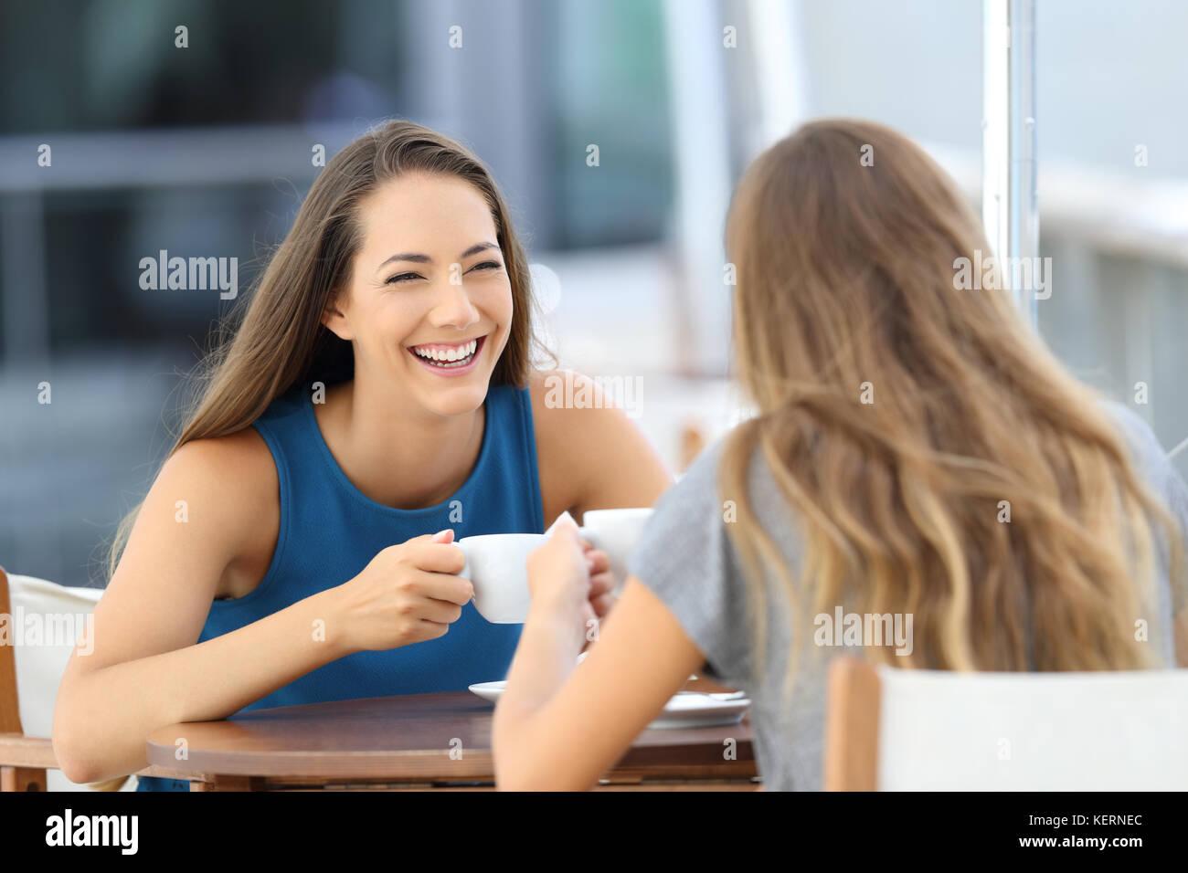 Dos amigos feliz hablando y riéndose sentados en un restaurante terraza Imagen De Stock