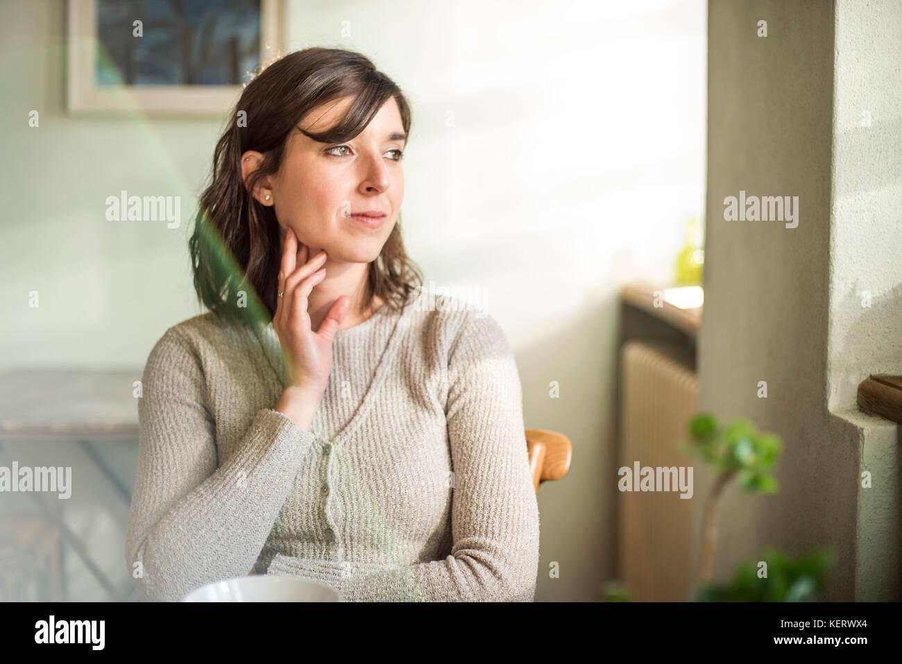 Contemplativo adulto joven mujer mirando por la ventana Imagen De Stock