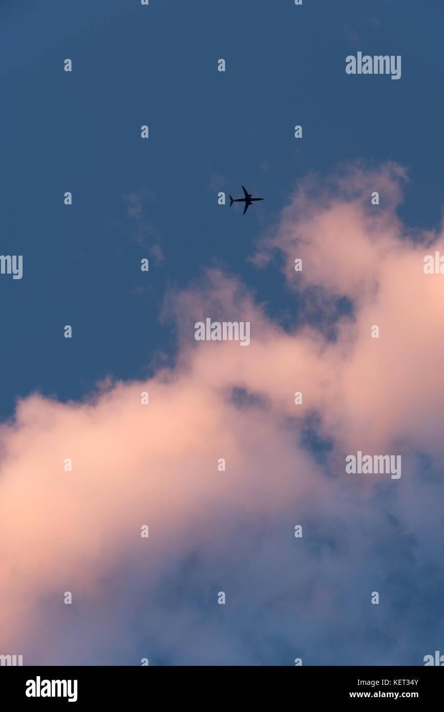 Sobrecarga jet acercando nubes atardecer contra un cielo azul profundo. Imagen De Stock