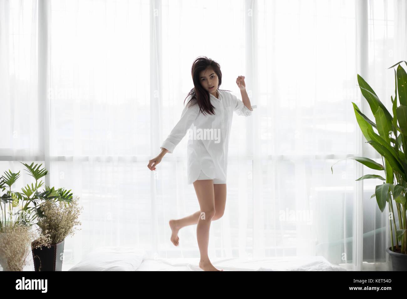 Mujer asiática hermosa joven sonriente y salta en su cama después de despertarse u Imagen De Stock