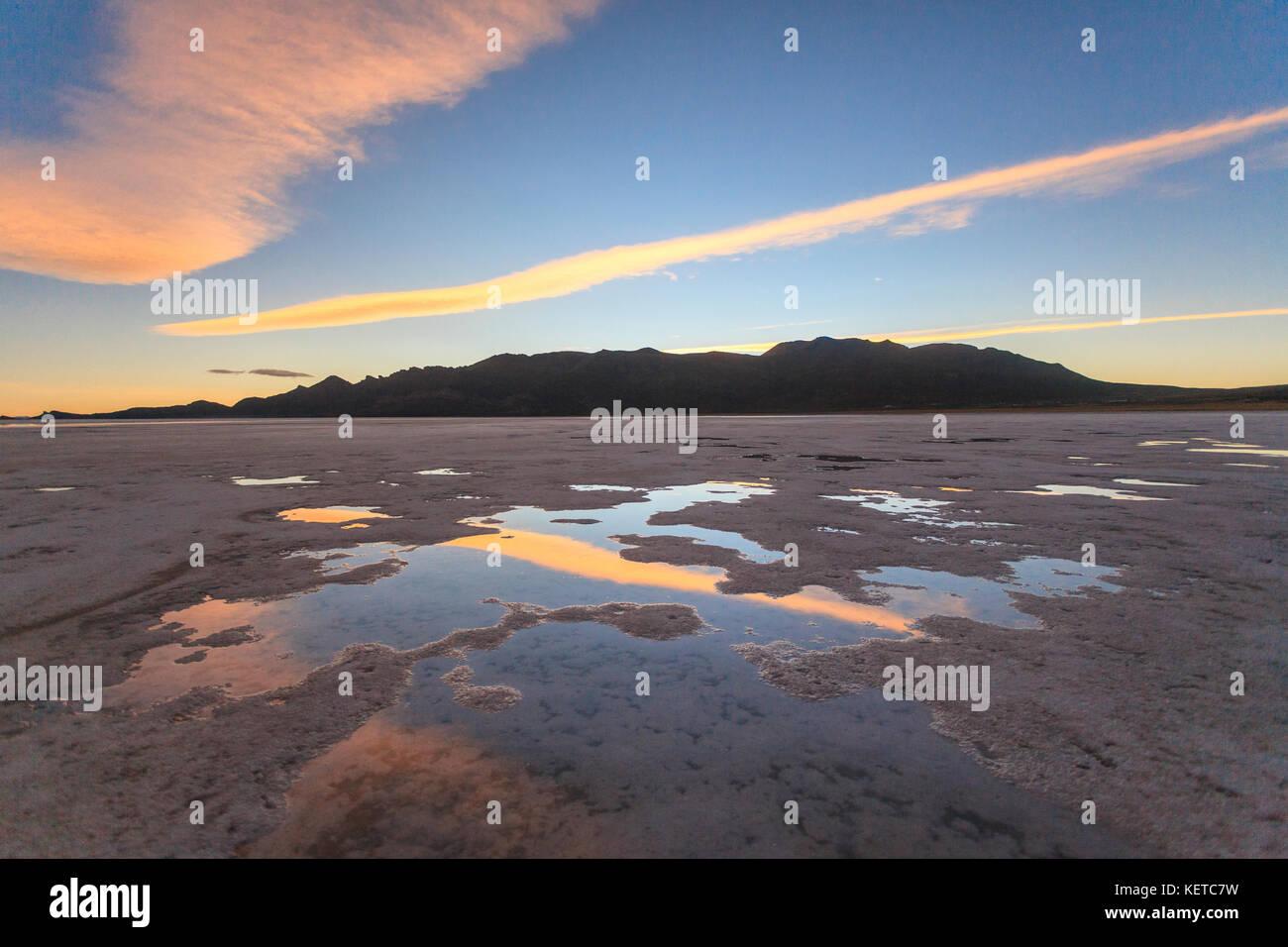 Nubes rosadas al atardecer se reflejan en la costra de sal del Salar de Uyuni, Sud Lípez bolivia América Imagen De Stock