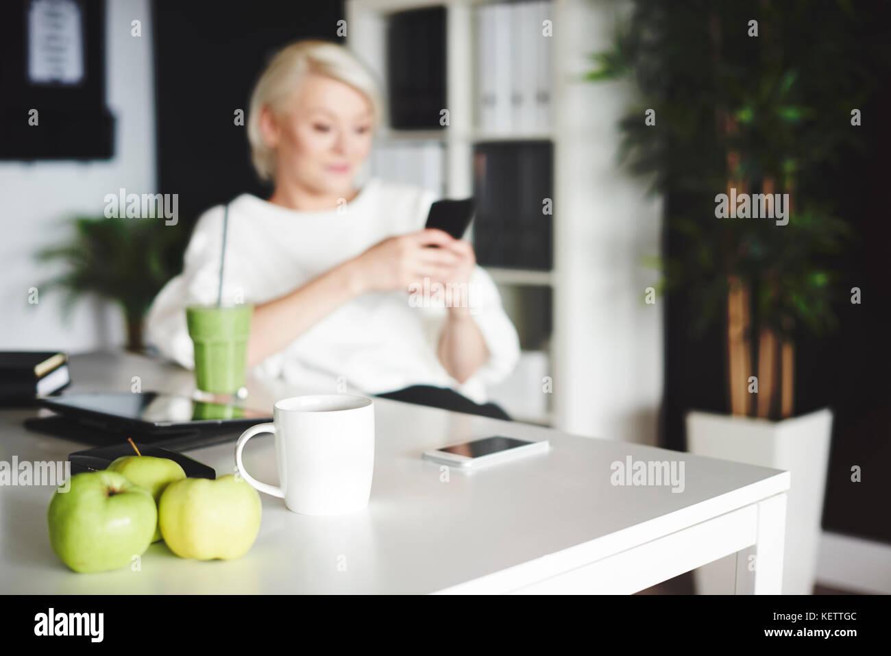 Mujer con fuzzy teléfonomóvil sentados frente al escritorio Imagen De Stock