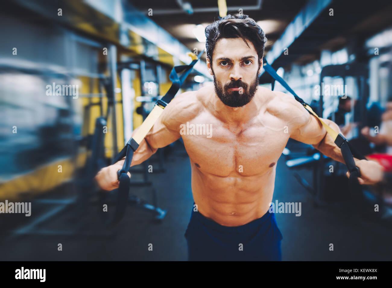 Joven apuesto hombre haciendo ejercicios en el gimnasio Imagen De Stock
