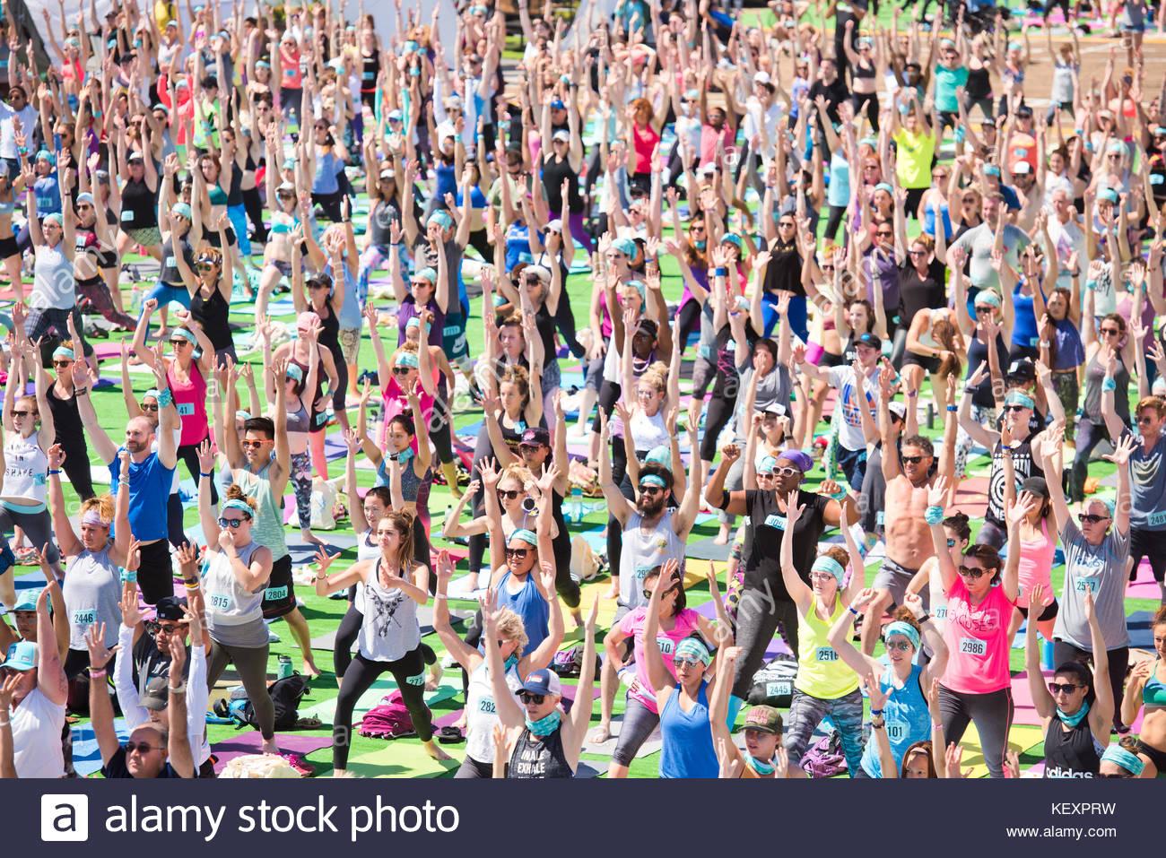 Gente realizando guerrero 1 durante el festival de yoga al aire libre en el muelle de Santa Monica Pier en Santa Imagen De Stock