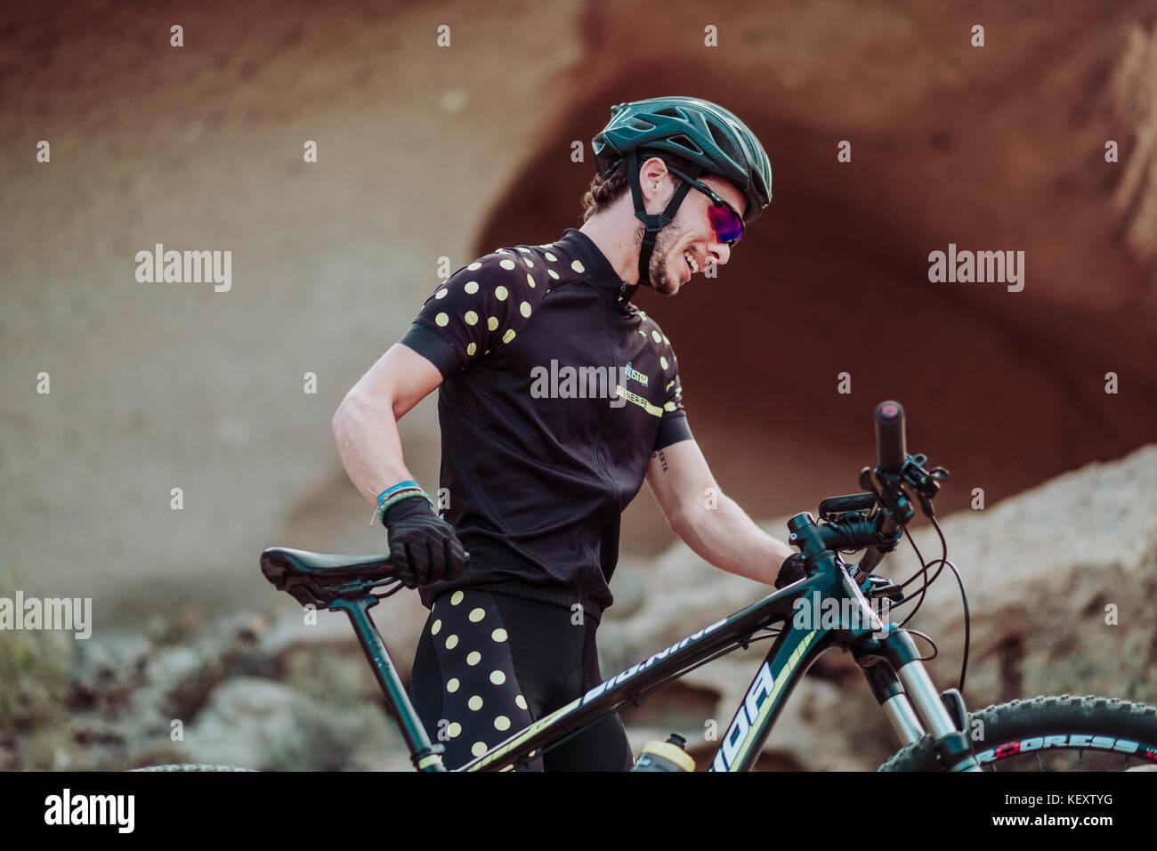 Hombre caminando en el desierto con su bicicleta de montaña, Tenerife, Islas Canarias, España Imagen De Stock