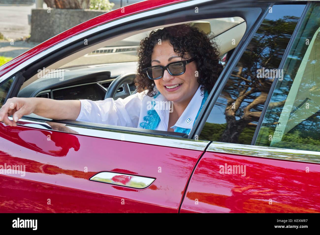 Feliz sonriendo Tesla sedán 'S' femenino, propietario de la estación de supercargador. Imagen De Stock