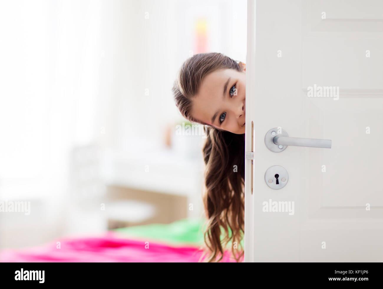 Feliz hermosa niña sonriente tras la puerta en casa Foto de stock
