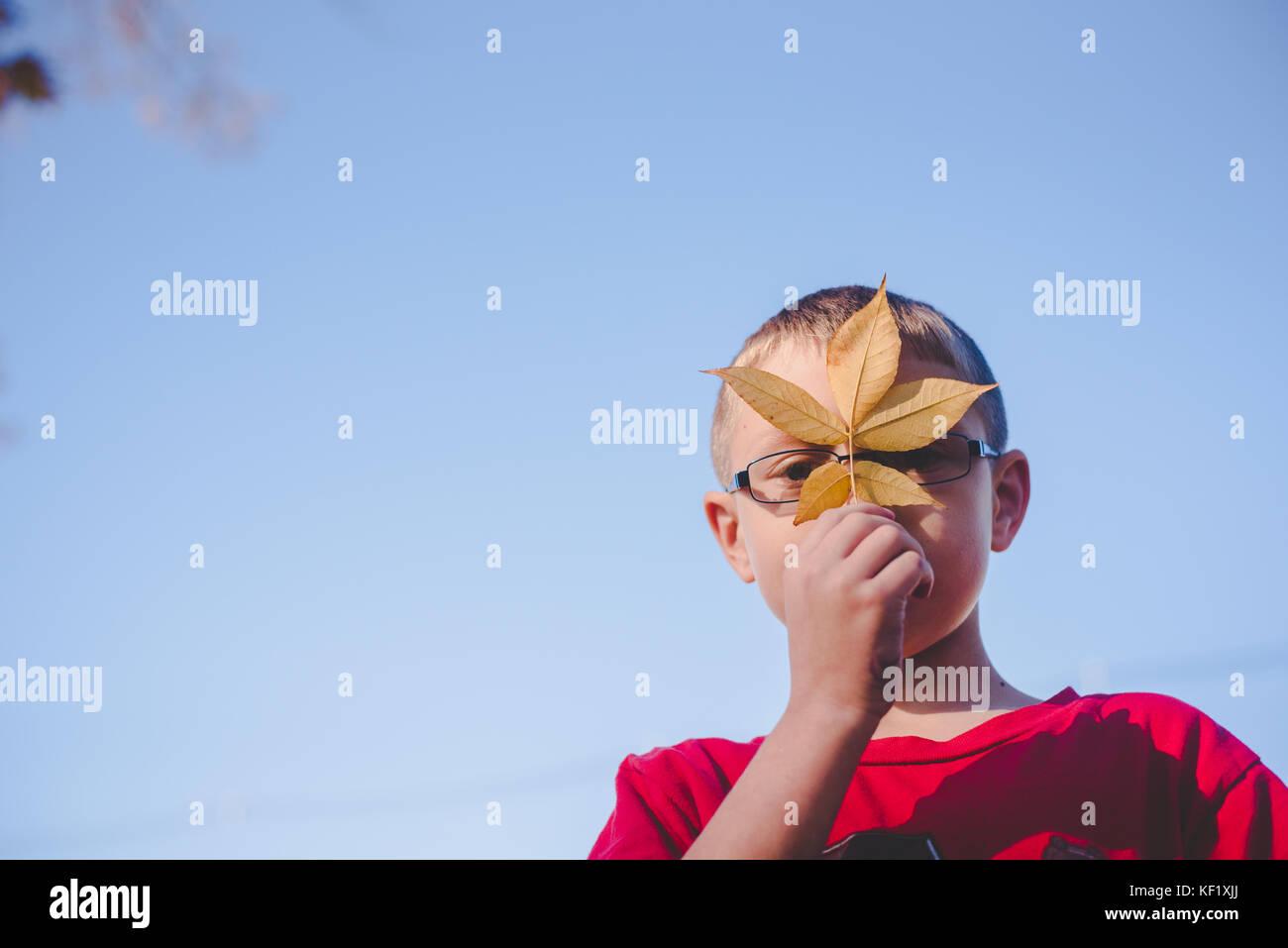 10-11 años de edad la celebración de hoja en la parte delantera de la cara Imagen De Stock