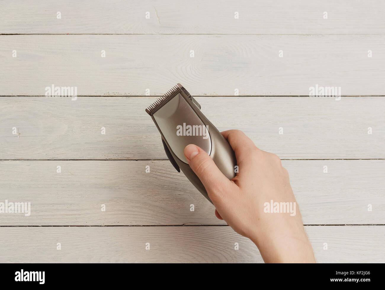 Mano de hombre sosteniendo cortapelos sobre fondo blanco de madera Imagen  De Stock a14cb86dbb0b