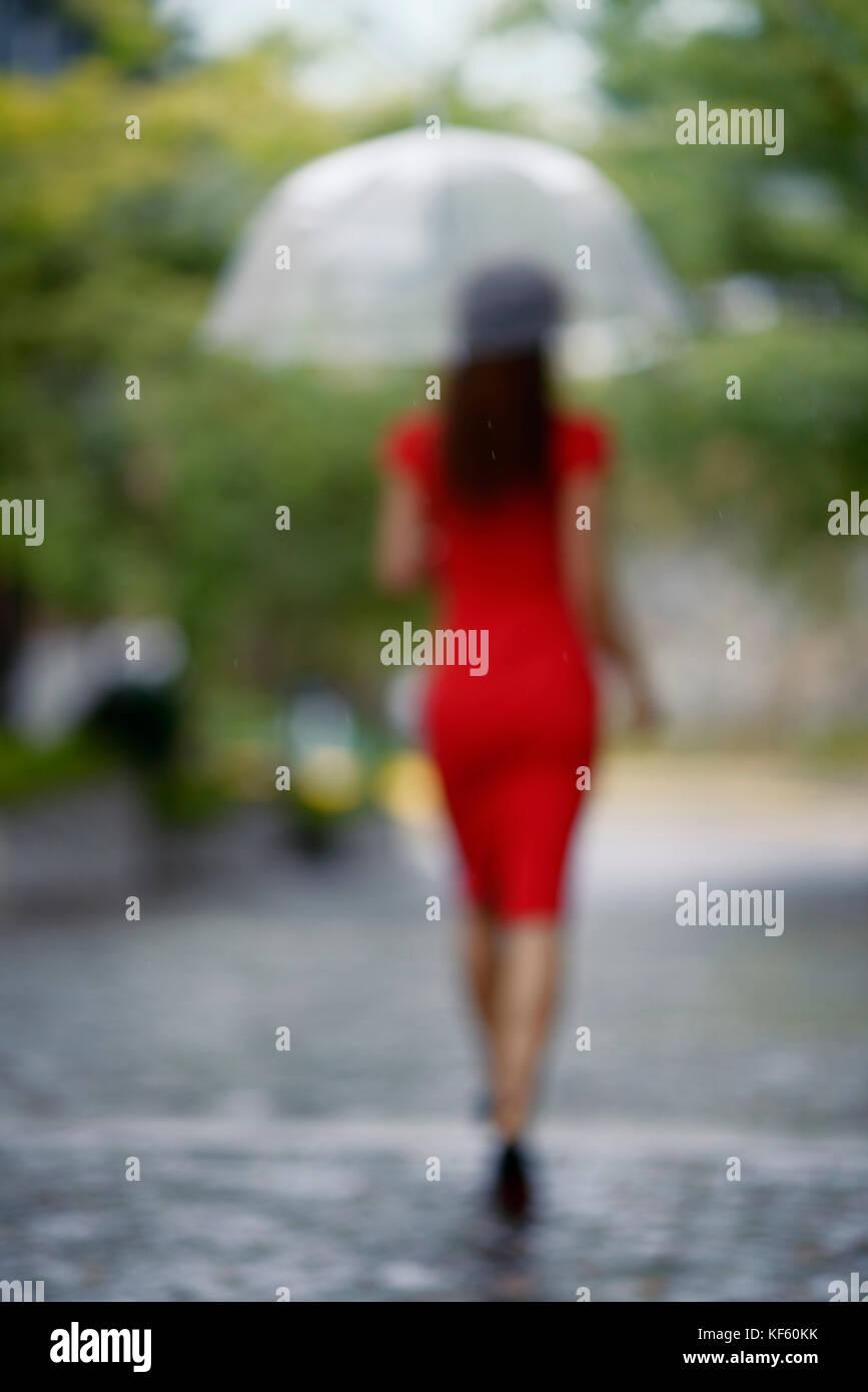 Fuera de enfoque vertical de la espalda de una mujer en un elegante vestido rojo con un paraguas caminando en la lluvia en una calle adoquinada Foto de stock