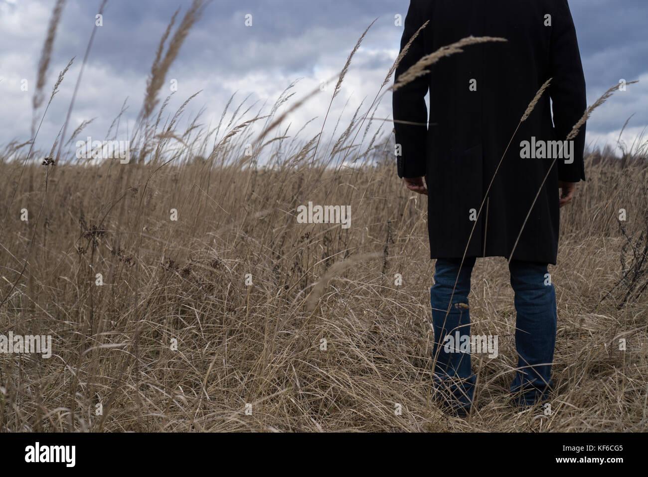 Volver Cerrar arriba de un hombre vestido con un abrigo de pie en un campo Imagen De Stock