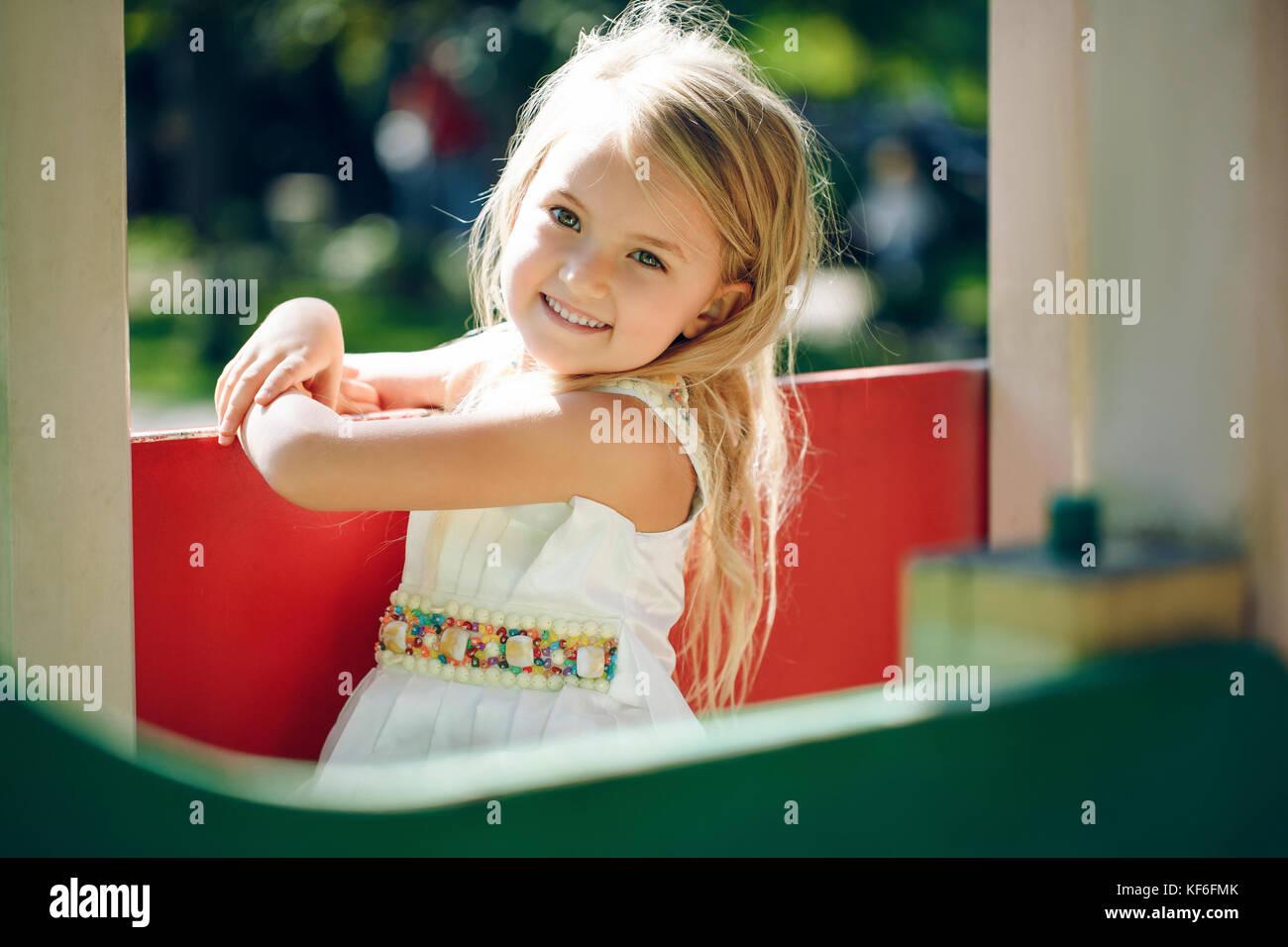 El verano, la infancia, el ocio, los gestos y el concepto de pueblo - feliz niña jugando en el patio de recreo Imagen De Stock