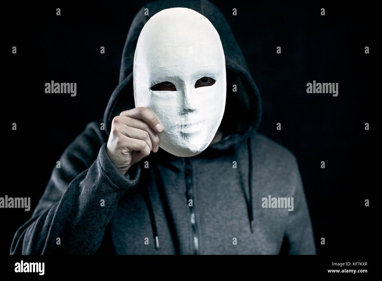 Hombre sujetando una máscara blanca para ocultar su rostro Foto de stock