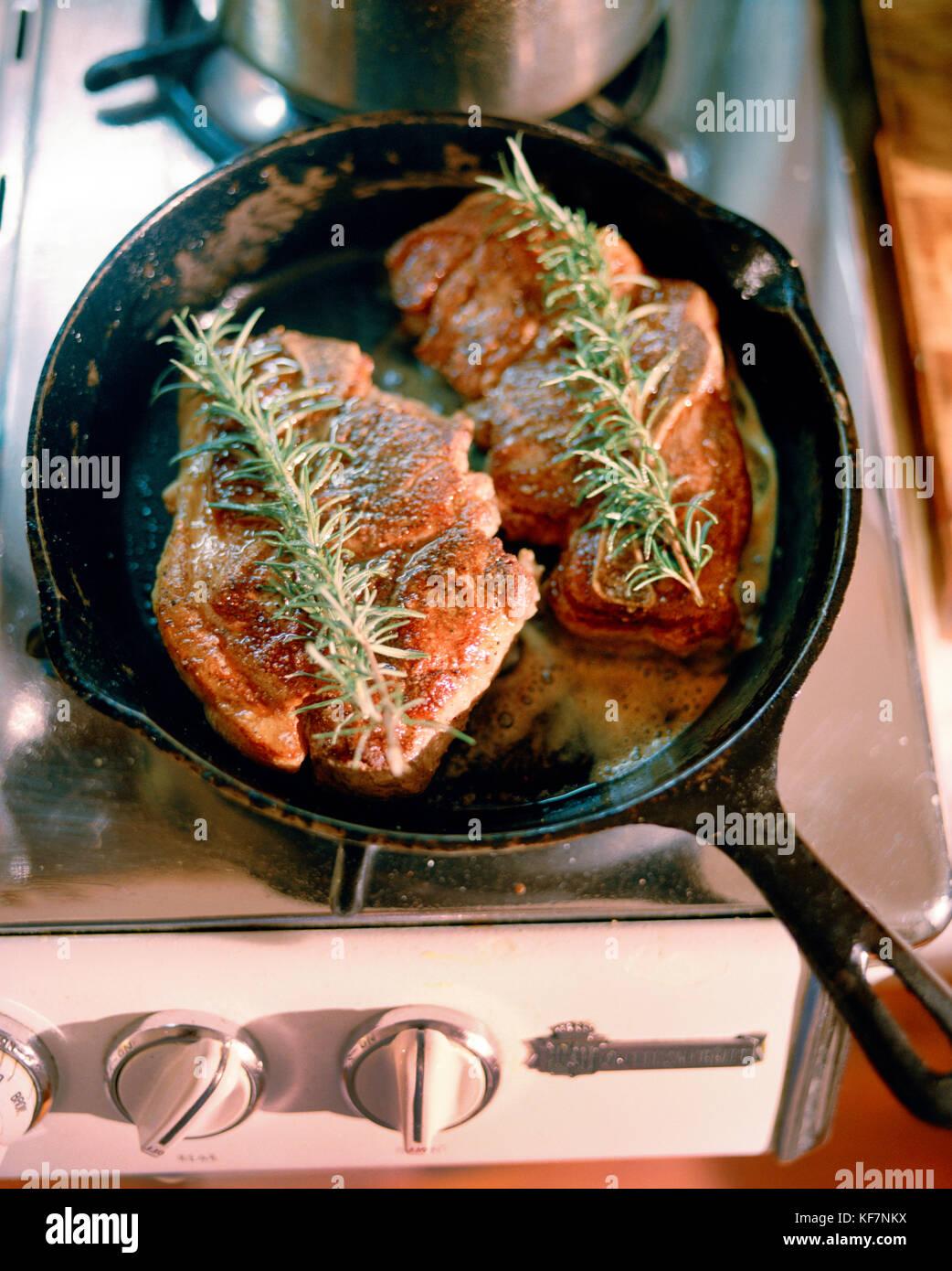Ee.Uu., California, Sonoma, cerdo está machacando en una cacerola de hierro fundido, casa de ladrillo bungalows Imagen De Stock