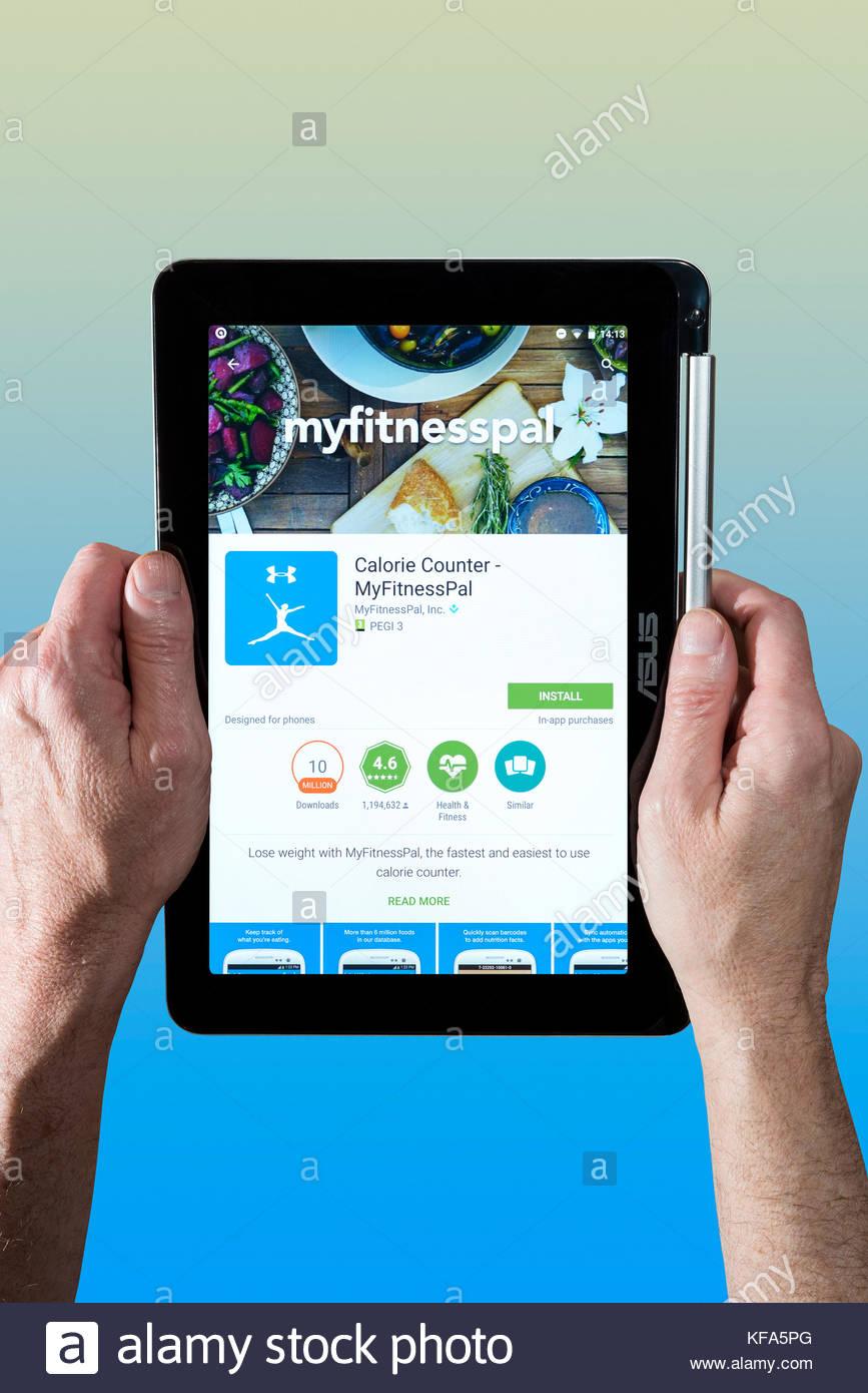 MyFitnessPal, el ejercicio y la salud app siendo utilizado por un Hombre sujetando un Chromebook. Cortar el fondo Imagen De Stock