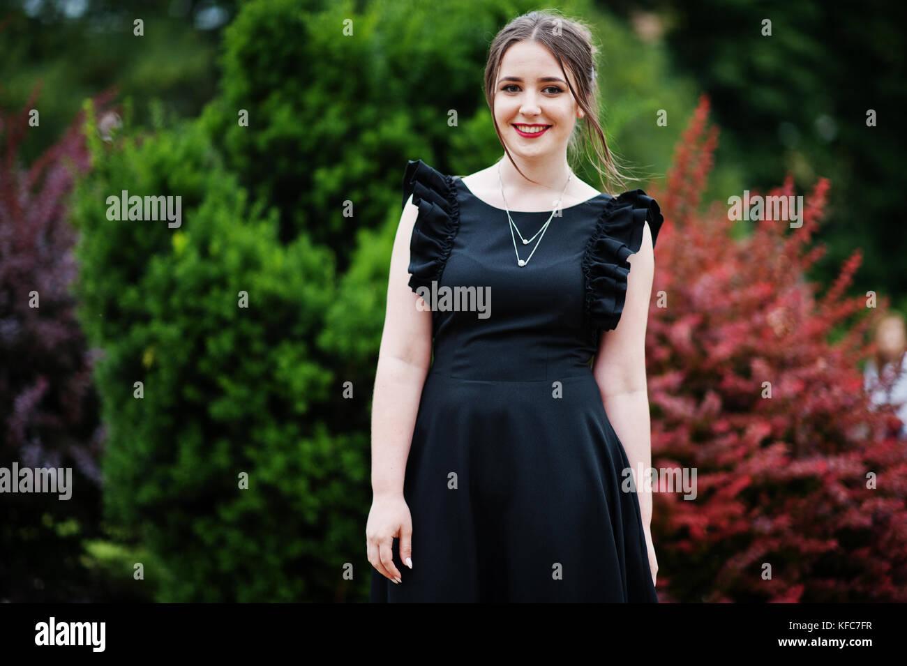 b2ea691e9 Retrato de una hermosa joven vestido negro caminando sobre el pavimento en  el parque en un