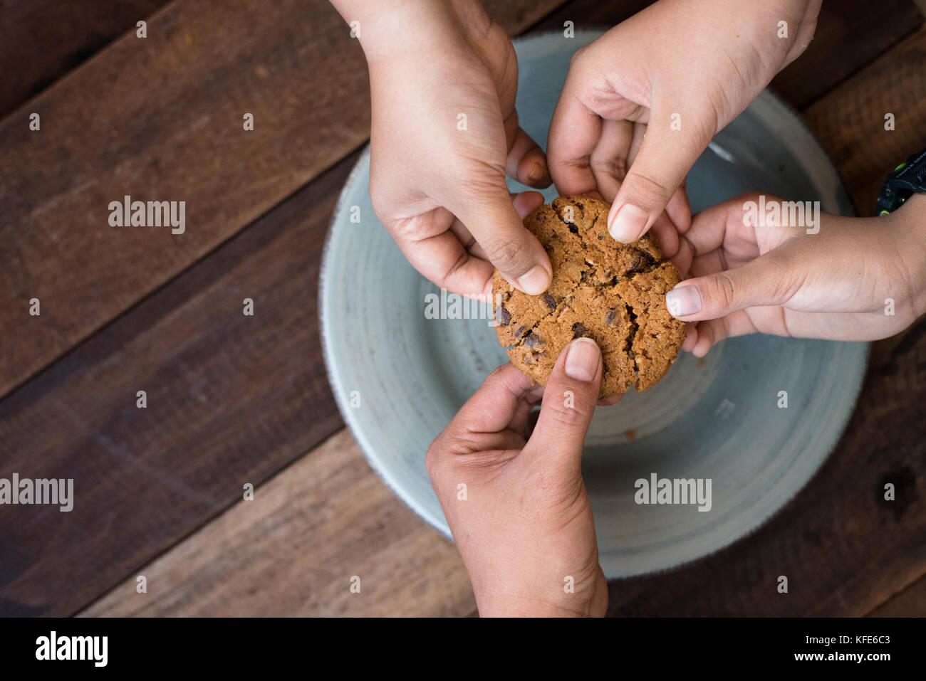 Concepto de reparto - familia compartiendo las cookies Imagen De Stock