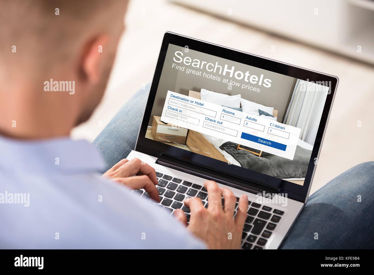 Close-up de una persona buscando hoteles con precios bajos en portátil Imagen De Stock