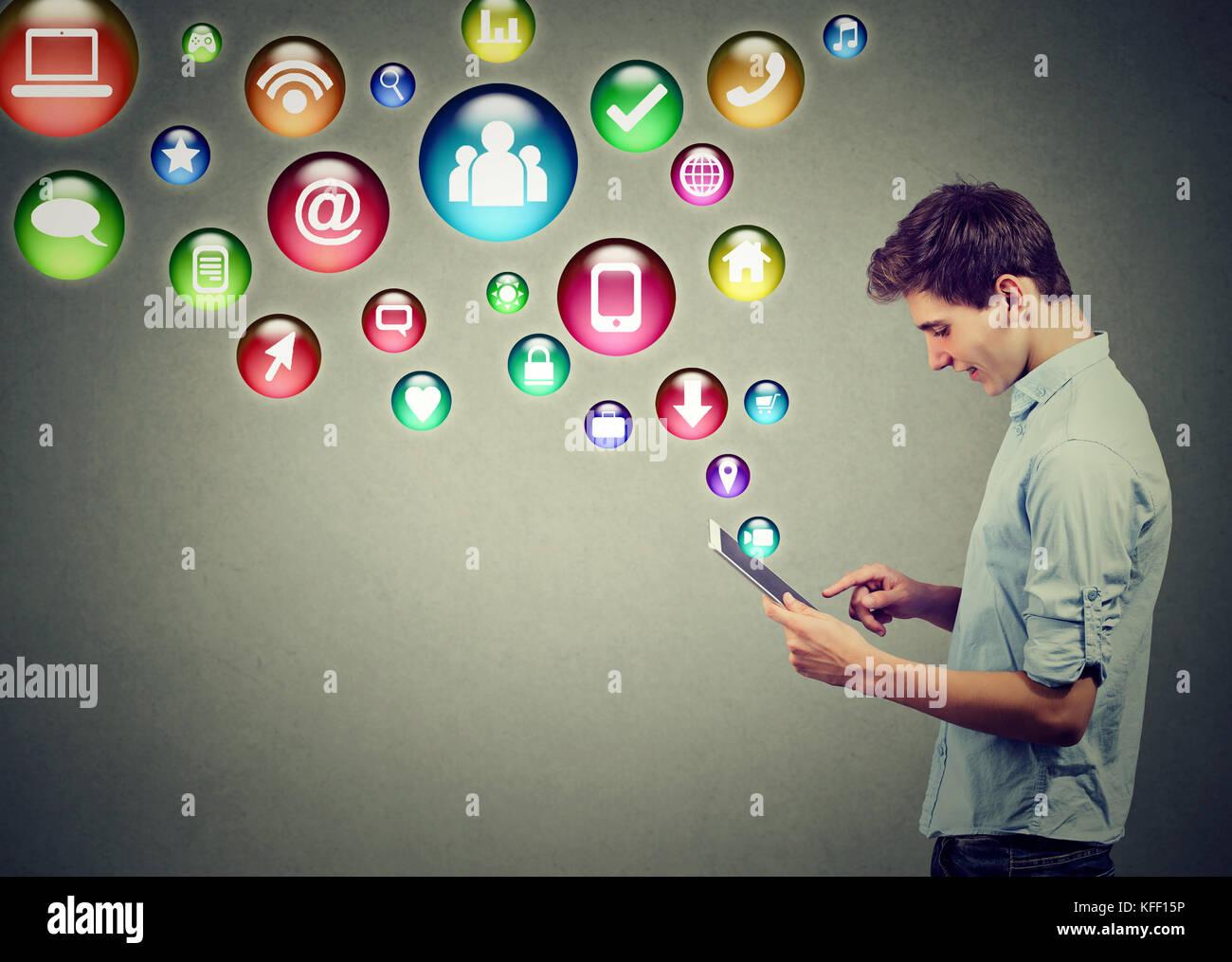 Tecnología móvil concepto de alta tecnología. El perfil lateral de un hombre joven con tablet pc Imagen De Stock