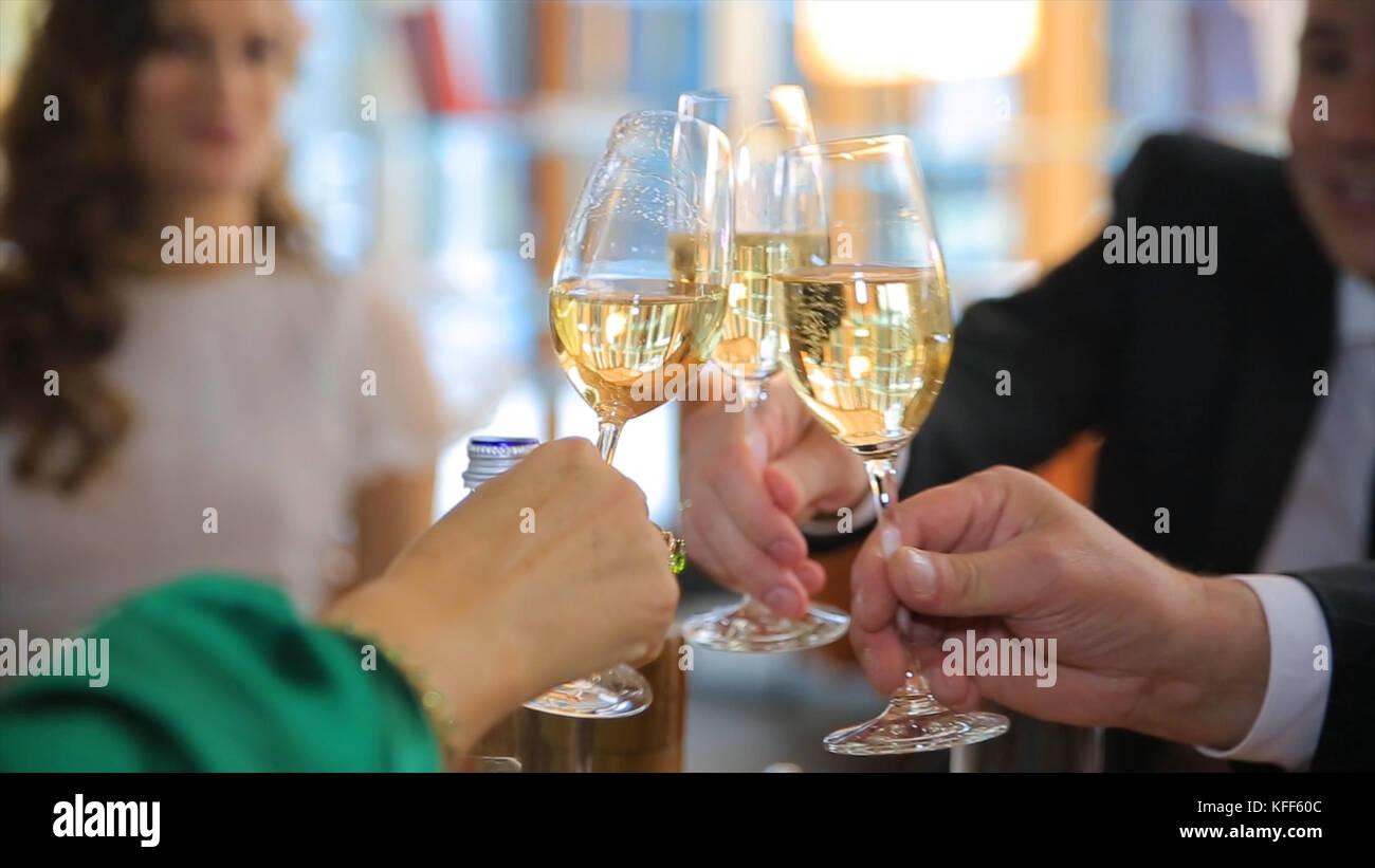 Manos sosteniendo las gafas y tostado, la gente saludos con una copa de champán. feliz momento festivo, celebración Imagen De Stock