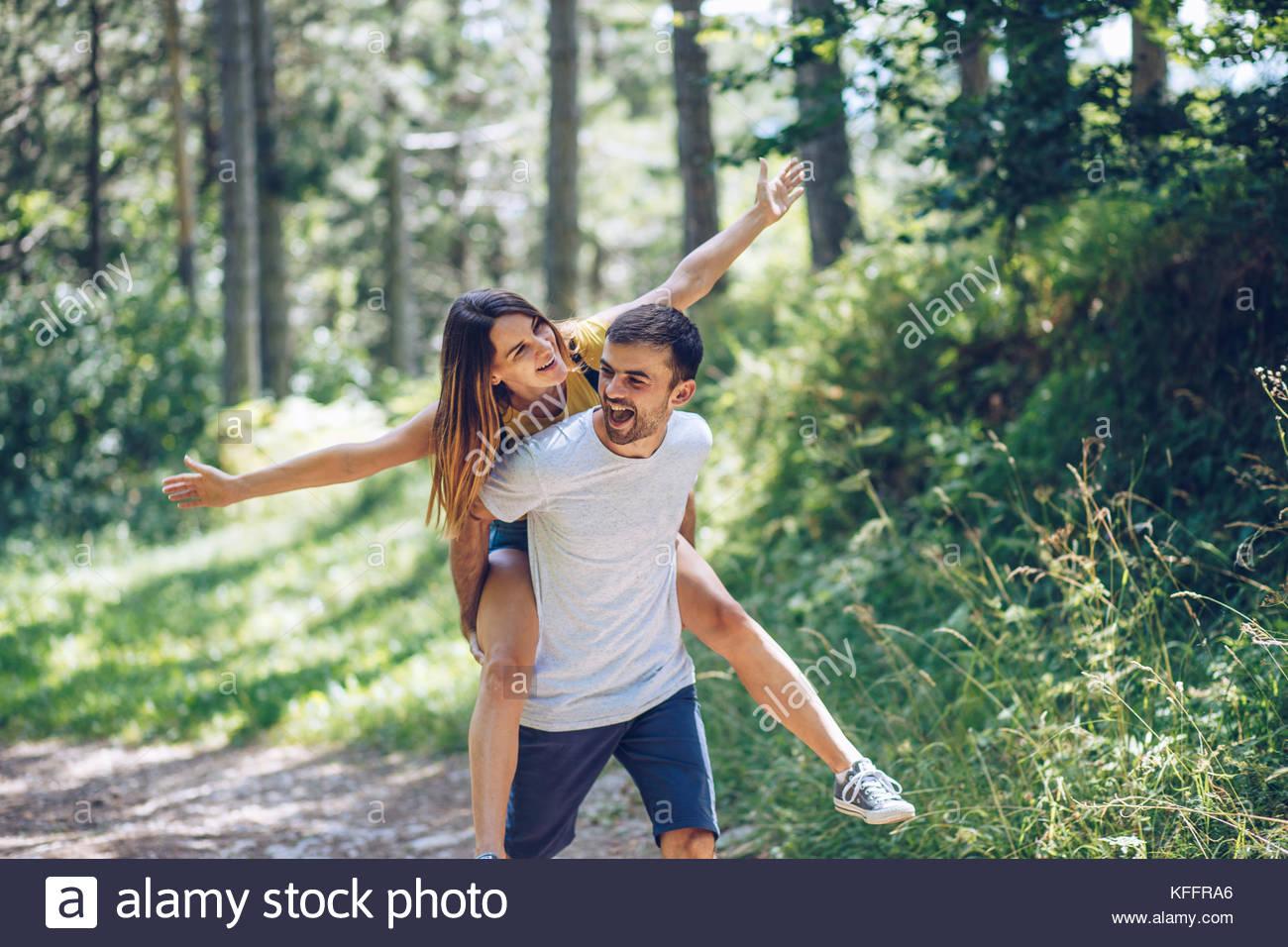 El hombre lleva una mujer piggyback Imagen De Stock