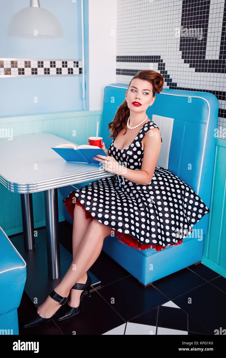 e7ed851e0 Retro (vintage) retrato de la guapa joven chica sentada en la cafetería con  un libro y bebidas estilo pin up retrato de niña en el vestido