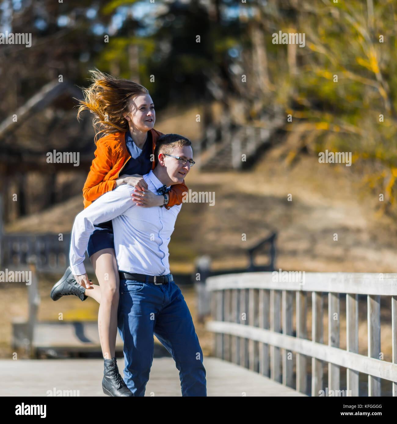 Feliz el hombre lleva a su novia en la parte posterior del puente sobre el río. Imagen De Stock