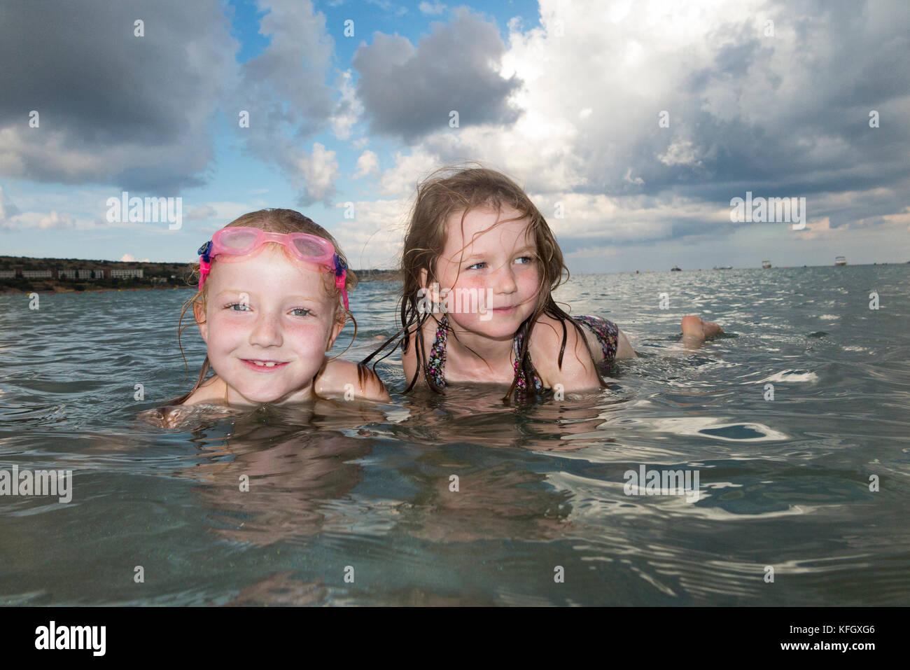 Hermanas de entre 7 y 5 años de edad nadar y jugar en Mellieha Bay Beach, en la costa norte de la isla principal Imagen De Stock