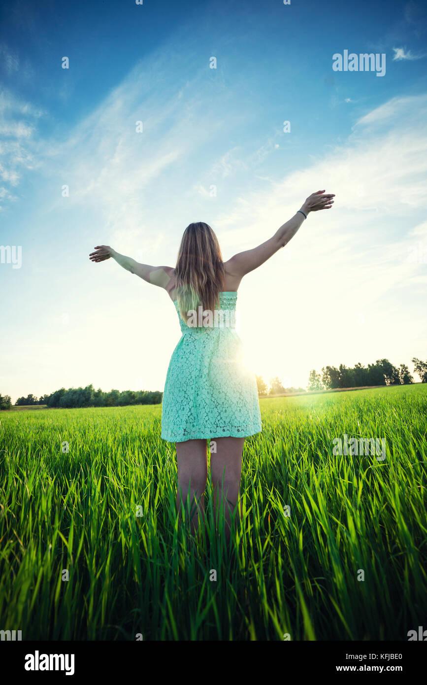 Felicidad mujer permanezca en exteriores bajo la luz del sol del atardecer Imagen De Stock